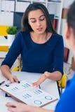年轻女性colar微笑在会议期间在办公室会议室 背景黑色五颜六色的概念玩偶小组工作 库存图片