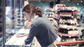 年轻女性costumer出来到冷冻机,比较价牌并且采取一盒饺子 女孩投入组装  影视素材