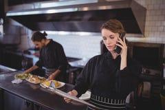 年轻女服务员谈话在智能手机,当准备食物的侍者在商业厨房里时 免版税图库摄影