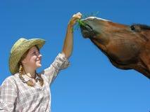 年轻女牛仔哺养的马 免版税图库摄影