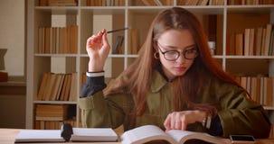 年轻女生看书和书写家庭作业画象入习字簿在图书馆里 影视素材