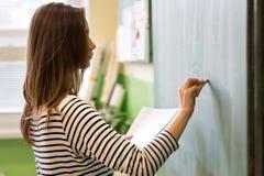 年轻女老师或一个学生文字算术惯例在黑板 免版税库存照片