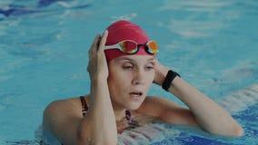 年轻女运动员从在水池的水涌现 她恢复呼吸,离开她的风镜并且看入 股票视频