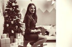年轻妇女获得与白色玩具马的乐趣自除夕 新年好假日 女孩坐反对绿色圣诞树 g 免版税库存照片
