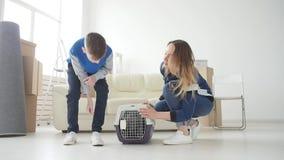 年轻妈妈和儿子有他们的猫的移动向一栋新的公寓 股票录像