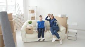 年轻妈妈和儿子有他们的猫的移动向一栋新的公寓 影视素材