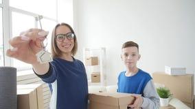 年轻妈妈和儿子移动向一栋新的公寓 股票录像