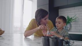 年轻妈妈和儿子饮用的汁液用在厨房的糖果 与儿子的愉快的母亲消费时间坐在慢的桌 股票录像