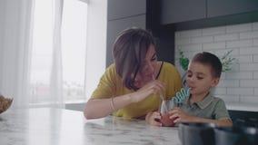 年轻妈妈和儿子饮用的汁液用在厨房的糖果 与儿子的愉快的母亲消费时间坐在慢的桌 影视素材