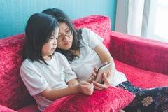 年轻妈妈和她的小女儿使用在沙发的一个智能手机 库存图片