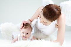 年轻妈妈和她的小婴孩女孩是天使 免版税图库摄影