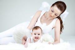 年轻妈妈和她的小婴孩女孩是天使 图库摄影