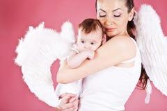 年轻妈妈和她的小婴孩女孩是天使 免版税库存照片