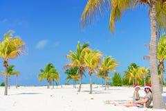 年轻妈妈和小女孩获得乐趣在热带海滩在坐在棕榈树附近的圣诞老人帽子 库存照片