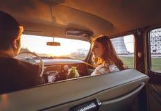 年轻婚礼夫妇坐的微笑在减速火箭的汽车里面和看彼此 结婚的容忍拥抱里面汽车 新娘 免版税库存图片