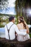 年轻婚礼夫妇坐长凳 库存图片
