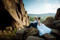 年轻婚礼夫妇紧接坐岩石 壮观的风景视图 库存照片