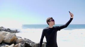 年轻嬉戏拿着电话和采取selfies的黑佩带的太阳镜的适合白种人人,当站立在多岩石的海滩wi时 股票录像
