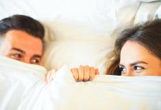 年轻嬉戏的夫妇获得乐趣在床-看害羞彼此的愉快的恋人在说谎在白色板料下的眼睛在te卧室 免版税库存照片