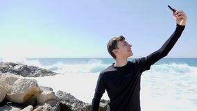 年轻嬉戏黑采取的selfies和微笑的适合白种人人,当在多岩石的海滩的身分与波浪击中和wate时 影视素材