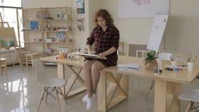 年轻孕妇图画绘画在艺术演播室,健康愉快的生活方式概念 股票录像