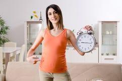 年轻孕妇在家 免版税图库摄影