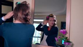 年轻孕妇离开从她的看在镜子的头发的卷发的人 股票录像