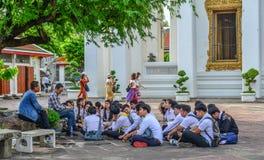 年轻学生参观Wat Pho寺庙 免版税库存照片