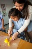 年轻学生在有他们的老师的厨房里采取一门基础课 v 库存图片