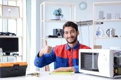 年轻安装工定象和修理微波炉 免版税库存图片