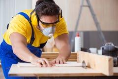 年轻安装工木匠与一把圆锯一起使用 库存照片