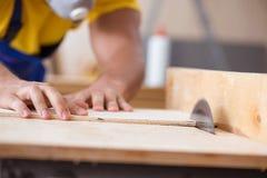 年轻安装工木匠与一把圆锯一起使用 图库摄影