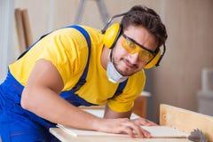 年轻安装工木匠与一把圆锯一起使用 库存图片