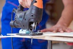 年轻安装工木匠与一把圆锯一起使用 免版税库存图片