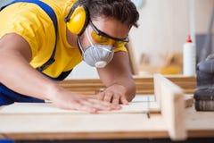年轻安装工木匠与一把圆锯一起使用 免版税图库摄影