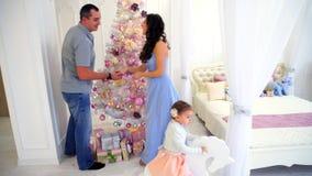 年轻家庭为即将来临做准备在假日树背景和大床庆祝的宽敞卧室光  股票录像