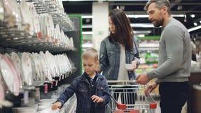 年轻家庭在厨具部门的超级市场选择碗,他们拿着比较他们的物品和 股票录像