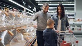 年轻家庭在超级市场选择在面包店部门的面包,小男孩采取从塑胶容器的大面包和 影视素材