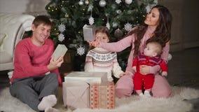 年轻家庭坐地板在欢乐圣诞树和观看的新年` s礼物附近 影视素材