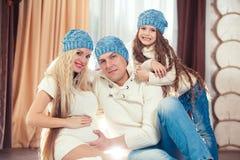 年轻家庭坐地板 在冬天毛线衣和帽子,圣诞节的概念 怀孕在一个木房子里 免版税库存照片