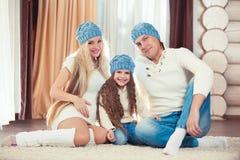 年轻家庭坐地板 在冬天毛线衣和帽子,圣诞节的概念 怀孕在一个木房子里 免版税库存图片