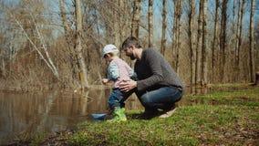 年轻家庭投入航行在水的一条玩具纸小船 影视素材