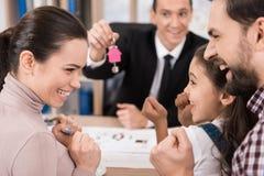 年轻家庭是愉快买新房在地产商办公室 采购的房子 安置销售额 库存图片