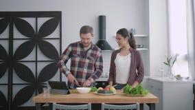 年轻家庭画象在厨房、愉快的丈夫和妻子里食物为与菜的早餐做准备在烹调桌上 股票视频