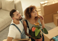 年轻家庭给一栋新的公寓带来有事的箱子 免版税库存图片