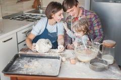 年轻家庭获得乐趣用面粉在杂乱厨房 库存照片