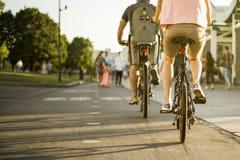 年轻家庭骑马在城市街道骑自行车在一个夏天晴天 免版税库存照片