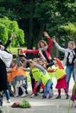 年轻小学生和他们的老师在一个公园做体育运动 库存照片