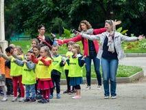 年轻小学生和他们的老师在一个公园做体育运动 库存图片