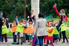 年轻小学生和他们的老师在一个公园做体育运动 免版税库存照片